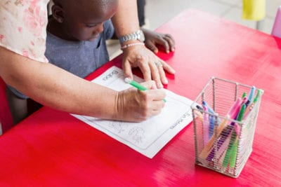 Woodlands Dairy - Teacher helping child to colour in his picture